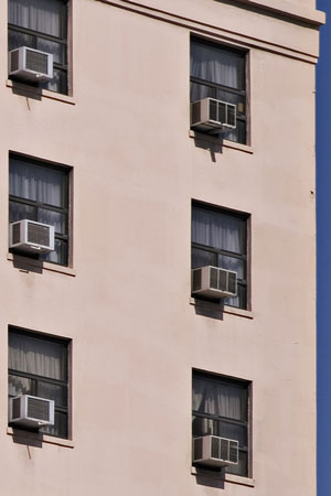 window air conditioners mounted in apartment building windows